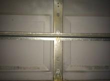 One piece garage door with two long metal rods